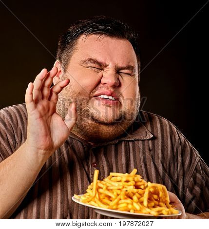 Diet failure of fat man eating french fries fast food. Portrait of overweight person who spoiled healthy meal . Junk meal leads to obesity. Disruption from diet concept. He is trying to go on a diet.
