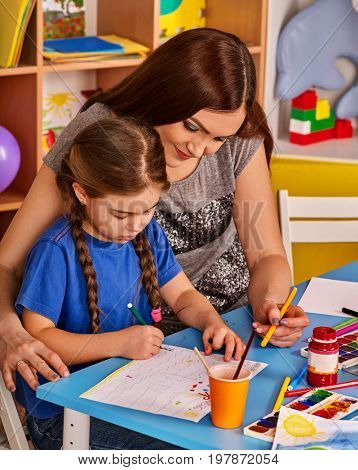 Small students girl with teacher painting in art school class. Child drawing by paints on table. Mom praises daughter in kindergarten. Craft drawing education develops creative abilities of children.