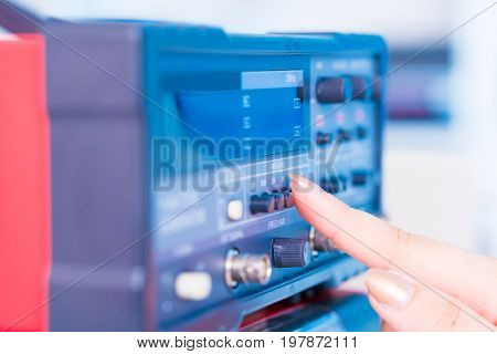 woman presses a button on an electronic measuring instrument