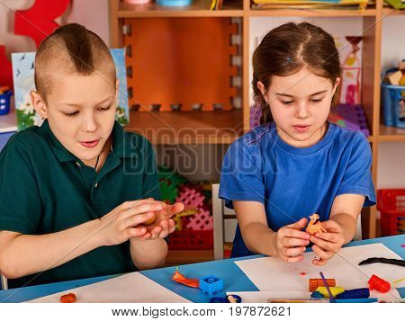 Small students with teacher painting in art school class. Child drawing by paints on table. Craft drawing education develops creative abilities of children. Zoo from plasticine.