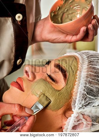 Mud facial mask of woman in spa salon. Massage with clay full face. Girl on with therapy room. Female lying wooden spa bed. Therapeutic mud is used for cosmetic masks. Home mask.
