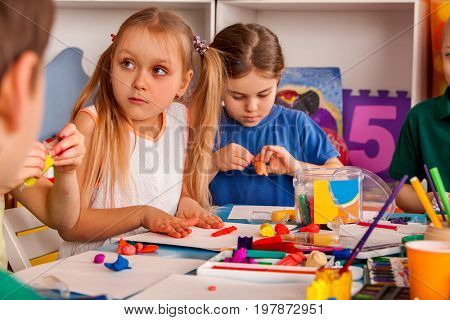 Child dough play in school. Plasticine for children. mold from plasticine in kindergarten .Kids knead modeling clay with hands in preschool. Preparing for a school exhibition of plasticine.