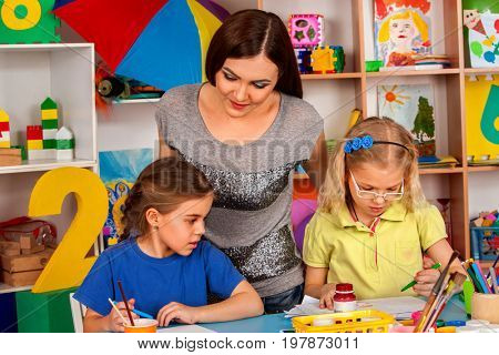 Kids playroom organization of children painting and drawing in kid's club. Craft lesson in primary school. Kindergarten teacher and small students work together. Preparing for a school exhibition of