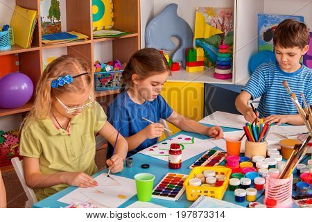 Small students girls painting in art school class. Children boy and girl drawing by paints on table. Children have fun at the children's club. Preparing for a school exhibition of plasticine.