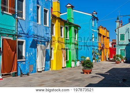 Old houses painted in yellow, blue, orange and green vibrant colors in Burano, Italy.