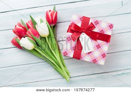 White and red tulips bouquet and gift box on wooden background. Top view with space for your greetings