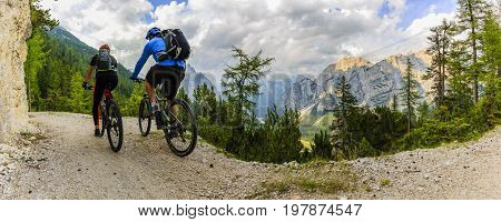 Mountain biking couple with bikes on track, Cortina d'Ampezzo, Dolomites, Italy