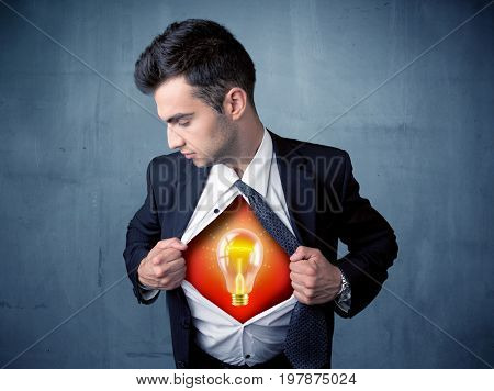 Businessman ripping off shirt and idea light bulb appears on his chest concept on backround