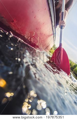 low angle view of a canoe paddle in the water on a sunny day during an active vacation