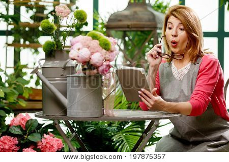 Woman with laptop among flowers