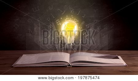 Shiny alphabet letters and yellow lightbulb hovering over open book