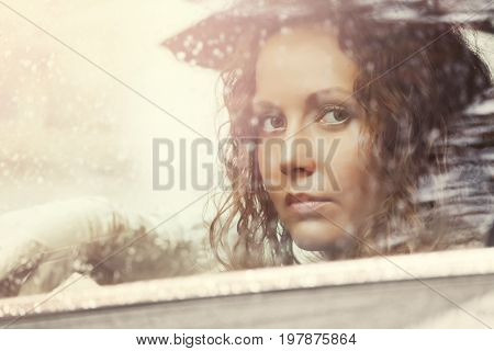 Sad woman looking out window driving a car in the rain