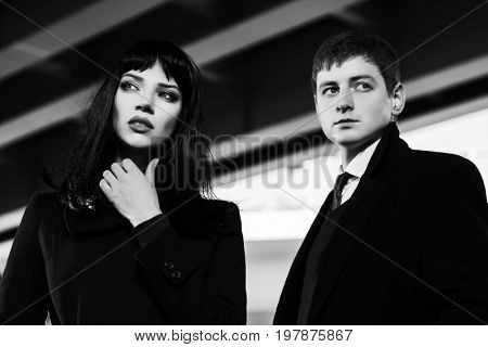 Young fashion man and woman walking in a city street. Stylish male and female model in black coat outdoor