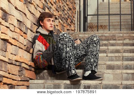 Sad young fashion hippie man sitting on the steps. Stylish trendy male model in a hooded sweater outdoor