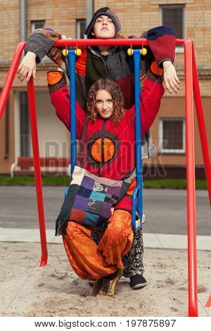 Young fashion hippie couple on the swing. Stylish trendy male and female models outdoor