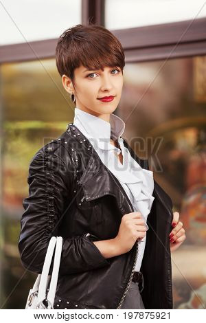 Happy young fashion woman with handbag next to mall window. Stylish female model in black leather jacket and white blouse outdoor