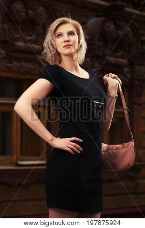 Happy young fashion blond woman in black dress walking in city street. Stylish female model with handbag outdoor