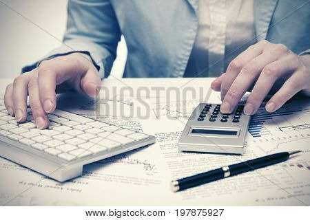 Financial accounting. Stock market graphs and charts. Business woman using calculator and computer keyboard