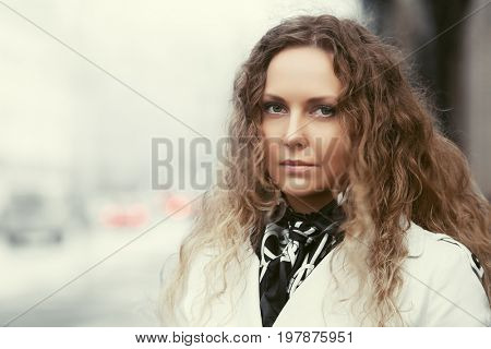 Beautiful fashion woman in white coat walking in city street. Stylish female model with long curly hairs outdoor