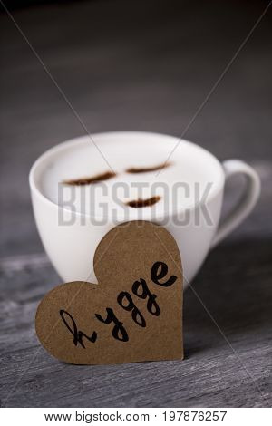 closeup of a cup of cappuccino with a happy face drawn with cocoa powder and a heart-shaped signboard with the text hygge, a danish and norwegian word for comfort or enjoy