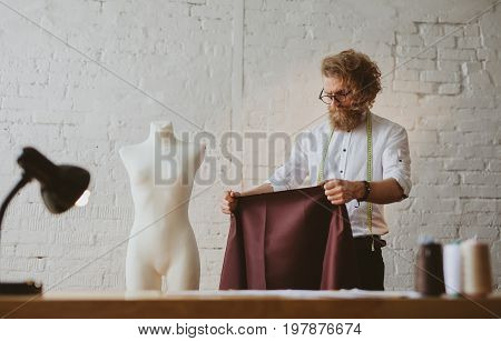 Bearded stylish man holding piece of fabric and working in parlour.