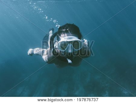 Young woman free diving in deep blue sea wearing in mask and snorkel.