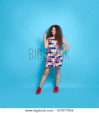 Young curly girl in colorful dress posing on blue background pointing up and smiling at camera.