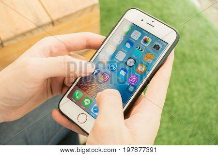 BANGKOK THAILAND - MAY 21 2017: Man using Iphone 7 white saree with application icons of social media on screen