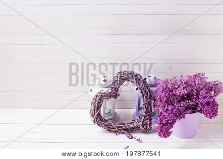 Flowers composition. Fresh splendid lilac flowers heart and lanterns with candles on white wooden background. Selective focus. Place for text.