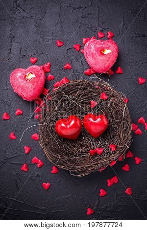 Hearts in nest and candles in form of heart on black slate background. Flat lay.Top view. St. Valentine day background.