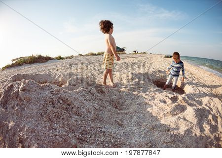 Boys Playing With Sand On The Beach.