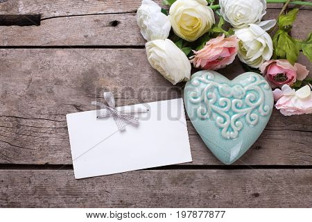 Pastel colors flowers decorative heart and empty tag on vintage wooden background. Selective focus. Place for text. Top view.