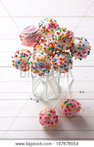 Colorful bright cake pops in jar on white wooden background. Selective focus. Vertical image.