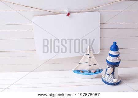 Decorative lighthouse wooden toy boat and empty tag on clothes line on wooden background. Selective focus. Place for text.
