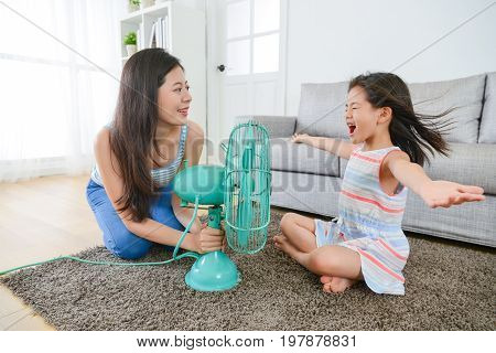 beautiful mother using electric fan let pretty little daughter enjoying cool wind and eliminate summer hot in living room.