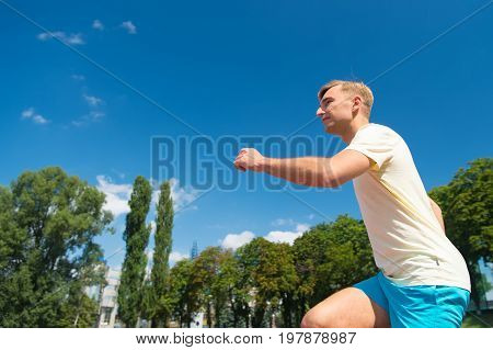 Sport and healthy fitness. Man running on arena track. Coach or trainer at workout. Guy sunny outdoor on blue sky. Runner on competition and future success.
