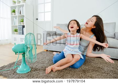 Happy Little Girl Sitting On Young Mother Legs