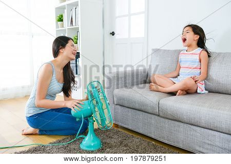 Little Girl Sitting On Sofa And Beautiful Woman