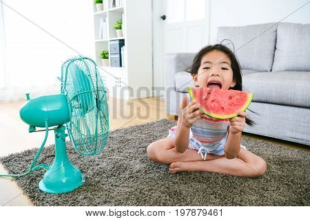 cute little female kid children sitting on floor eating fresh watermelon and blowing electric fan cool wind enjoying summer day.