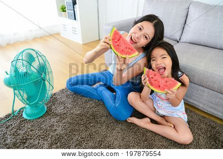 high angle view photo of sweet mother with daughter eating watermelon together and using electric fan making cool wind enjoying summer season.