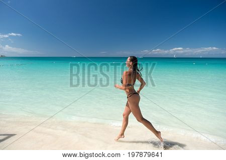 Woman in bikini running on beach with white sand turquoise sea or ocean water and blue sky on sunny day on natural environment. Sun tanning bathing. Summer vacation. Rest relaxing active leisure