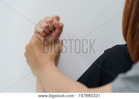 Man hand oppressing or pressing woman wrist on the wall - woman violence concept