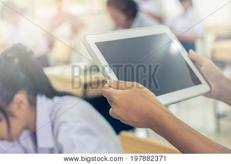 blurred of Asian girls student testing in exercise exams answer on a tablet computer in elementary high school lesson in class room for test exams online education by finger clicking