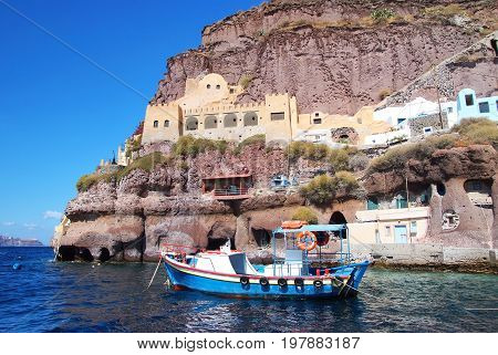 Santorini Greece - JULY 15 2017: sailing boat in bay of Santorini island on water near building on mountain