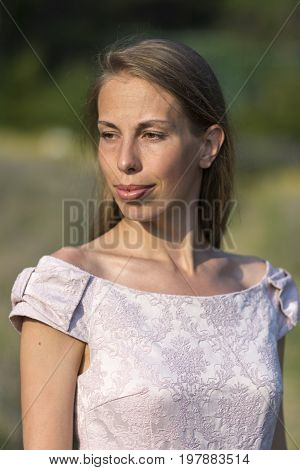 Portrait of a beautiful woman in a pink dress, outdoor. Stock photo