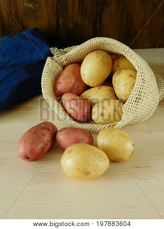 Potatoes are scattering out of a sack on a wooden background. Harvest picking concept
