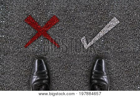 a salaman shoes standing on concrete road with red wrong mark and white check mark. who confusing to unknow the good or bad way for his life concept.