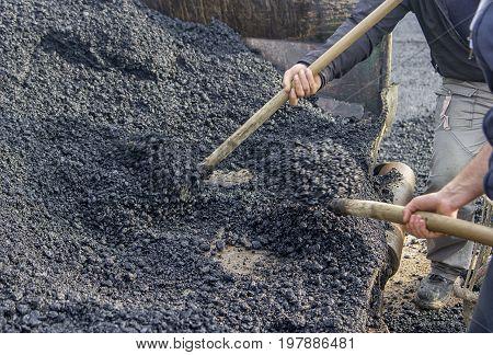 Asphalt Workers With A Shovel Filling Wheelbarrow With Asphalt 2
