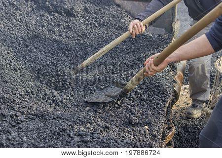 Asphalt Workers With A Shovel Filling Wheelbarrow With Asphalt 3
