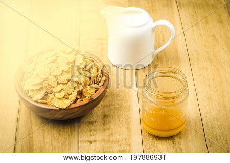 flakes honey and a creamer on a rustic background. Toned